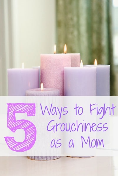 Group of purple candles burning in front of mirror.